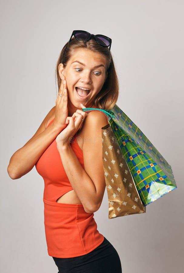 Jeune dame choquée de brune dans des lunettes de soleil de port d'un T-shirt rouge posant avec des sacs à provisions et regardant image stock