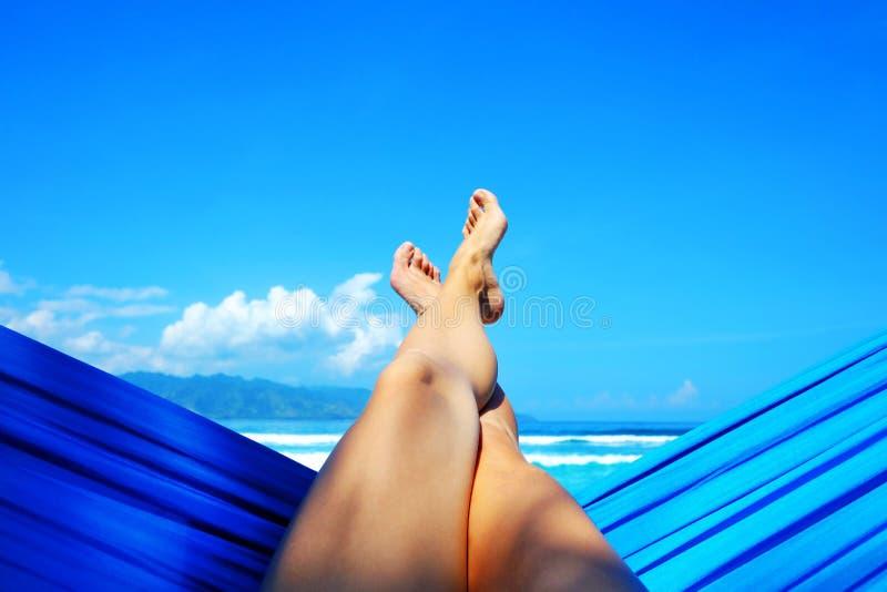 Jeune dame détendant dans l'hamac sur la plage sablonneuse avec la vue sur les îles tropicales à distance Concept de vacances et  images stock