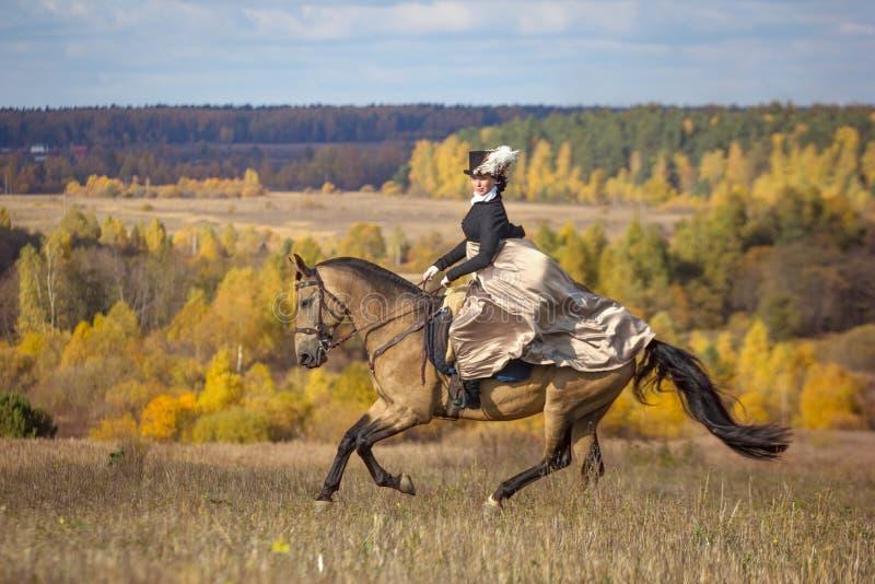 Jeune dame dans la robe du 19ème siècle montant un cheval akhal de teke images stock