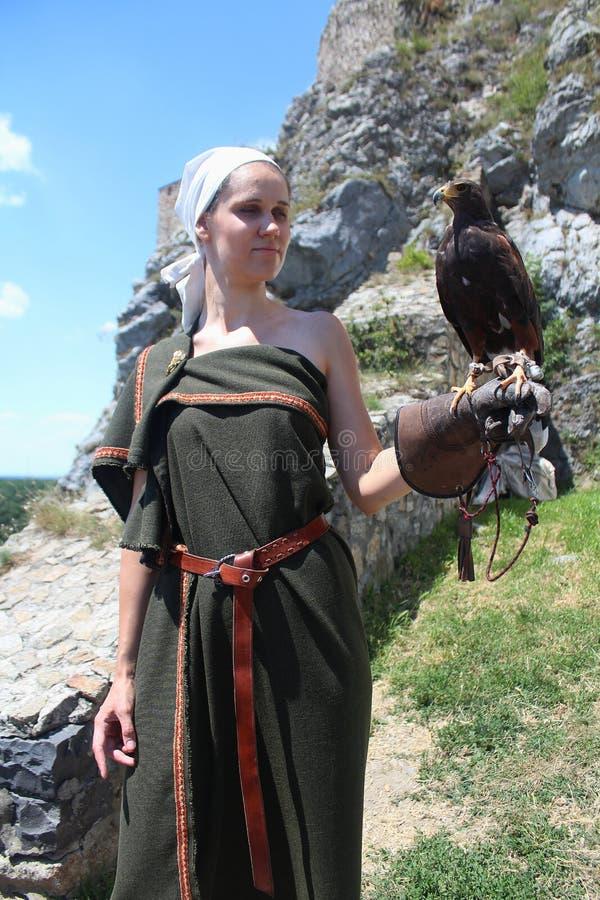 Jeune dame dans un costume historique avec un unicinctus de Parabuteo de faucon du ` s de Harris photo stock
