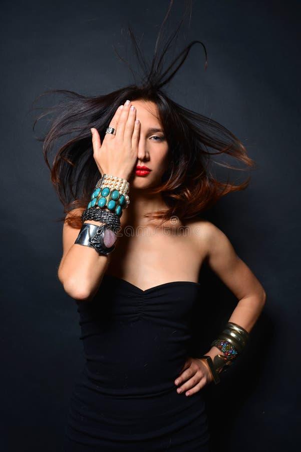 Jeune dame de brune avec les accessoires de luxe d'isolement sur le fond noir photographie stock libre de droits