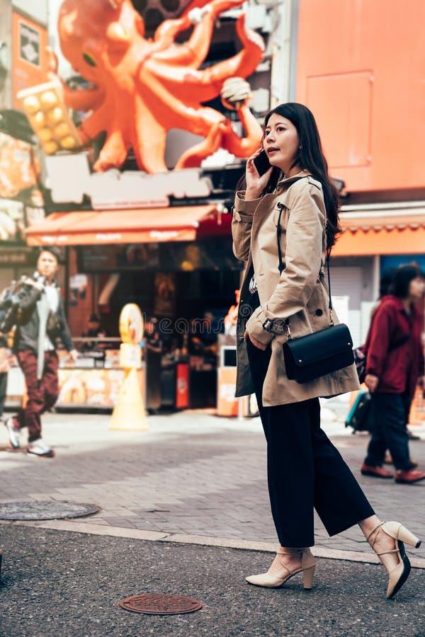 Jeune dame de bureau parlant sur le smartphone photo stock