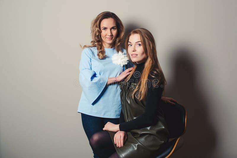 Jeune dame deux élégante posant sur le fond gris Concept d'association, d'amitié, de mode et de mode de vie Mode de femme photos stock