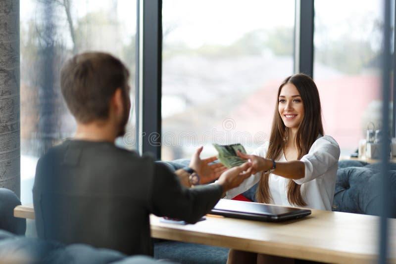 Jeune dame donnant l'argent à l'homme Concept d'affaires images stock