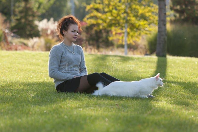 Jeune dame et garçon avec le chat de Maine Coon photographie stock libre de droits