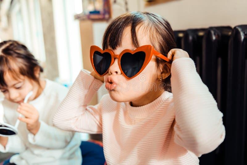 Jeune dame expressive essayant sur les lunettes de soleil en forme de coeur images stock