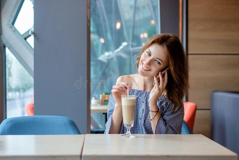 Jeune dame gaie au restaurant parlant au téléphone photo stock