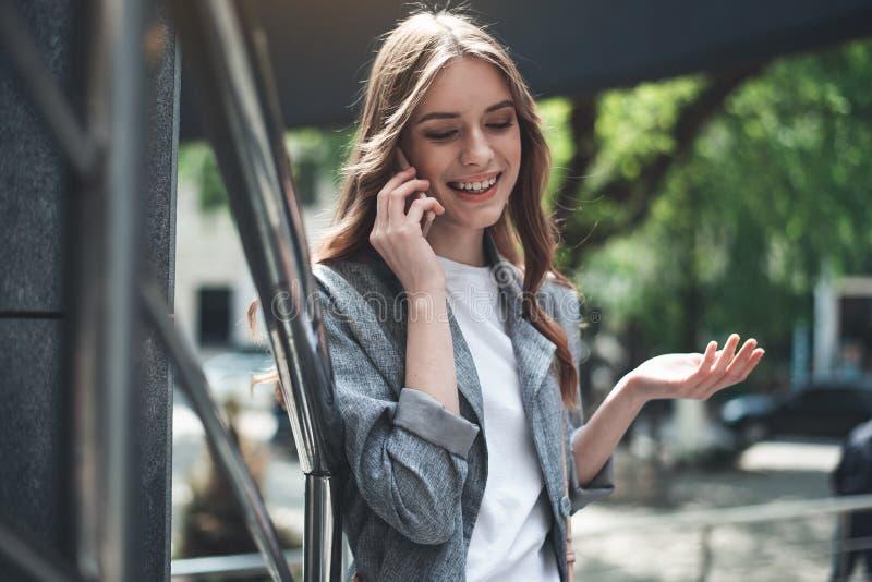 Jeune dame gaie parlant au téléphone près de la rampe images stock