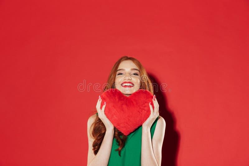 Jeune dame heureuse rousse tenant le coeur de peluche dans des mains images libres de droits