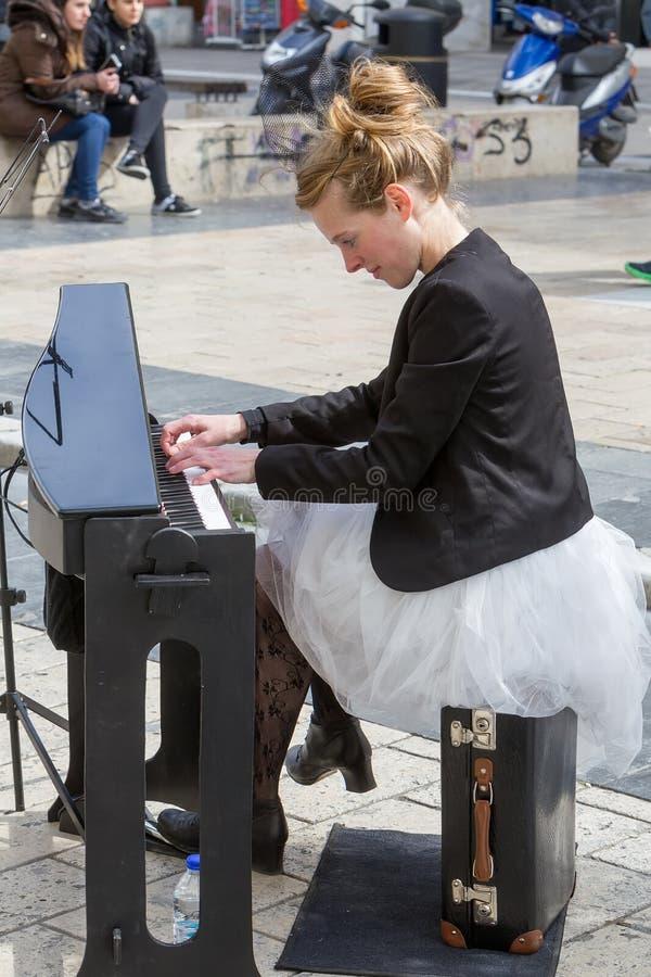 Jeune dame jouant le piano électrique à la place d'Aristotelous image libre de droits