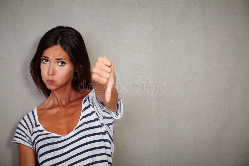 Jeune dame mécontente montrant le signe de désapprobation photos stock