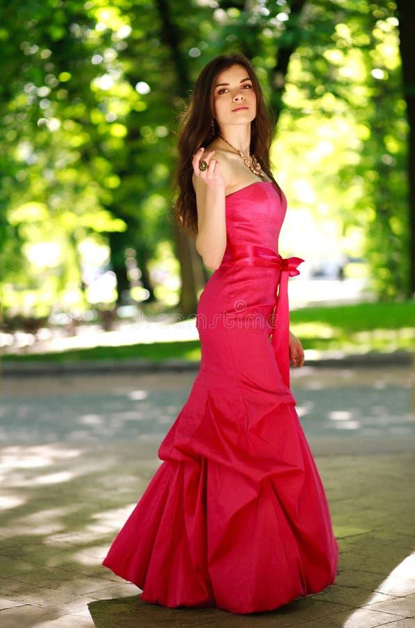 Jeune dame magnifique dans la longue robe de luxe en parc d'été images stock