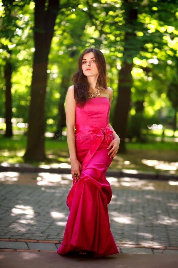 Jeune dame magnifique dans la longue robe en parc d'été photographie stock