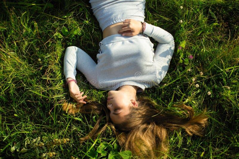Jeune dame mignonne se trouvant sur l'herbe verte photos stock