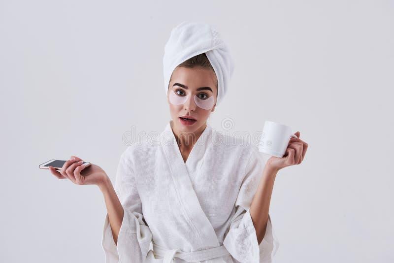 Jeune dame perplexe avec des corrections sous des yeux tenant le téléphone portable et la tasse de café image stock