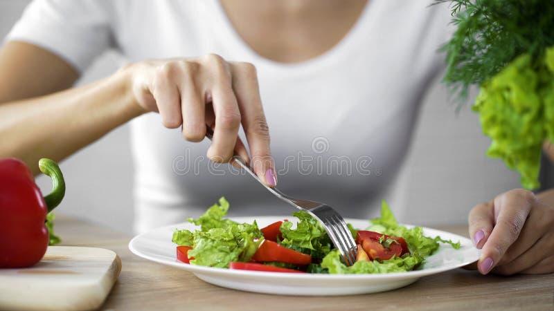 Jeune dame prenant la fourchette de salade de tomate du plat de dîner, casse-croûte sain, vitamines photographie stock