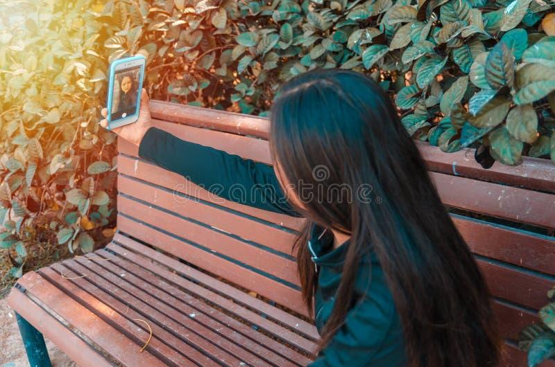 Jeune dame prenant le selfie sur un banc photo libre de droits