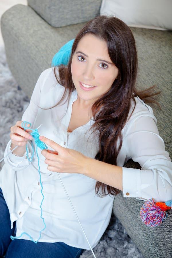 Jeune dame reposée sur le tricotage de plancher images stock