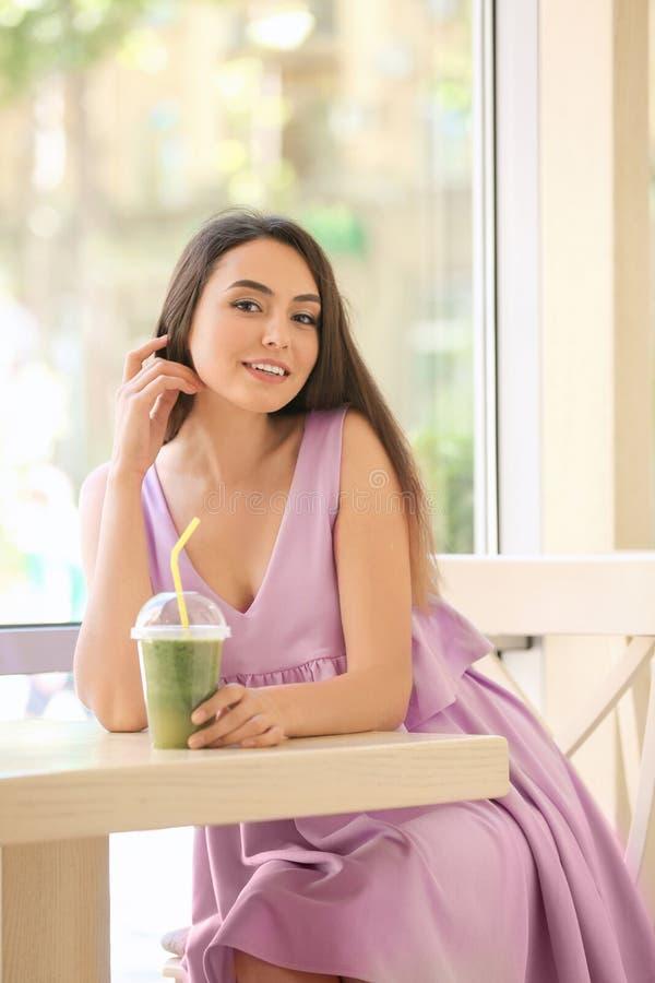 Jeune dame romantique appréciant le smoothie savoureux image stock