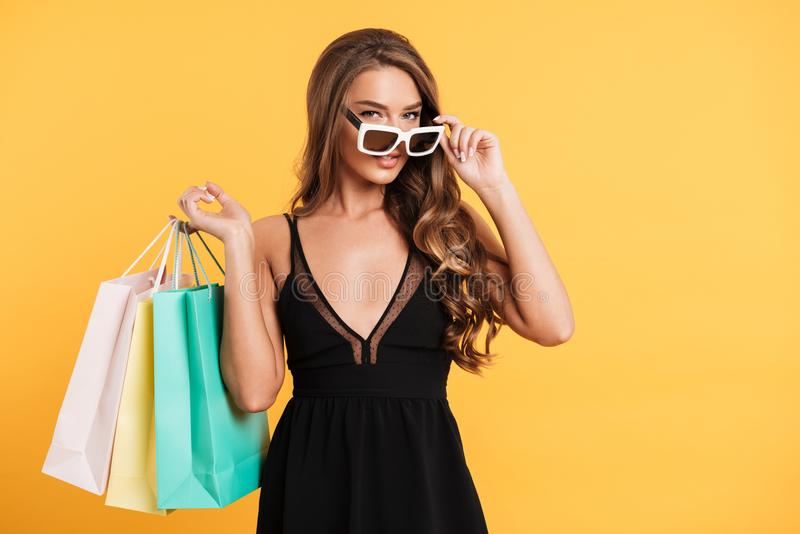 Jeune dame sérieuse dans la robe noire tenant des paniers photographie stock libre de droits