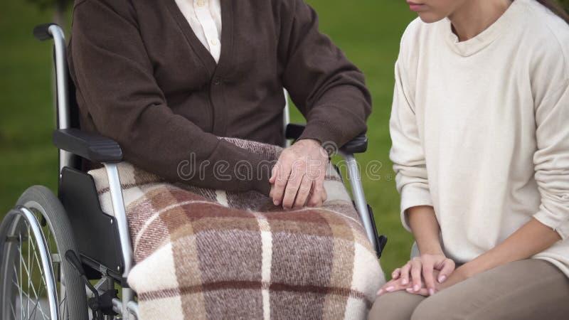 Jeune dame s'asseyant près de l'homme supérieur dans le fauteuil roulant, l'appui de famille et le soin, amour images libres de droits