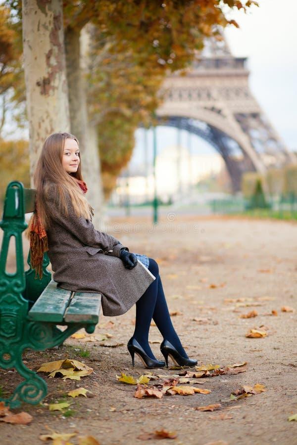 Jeune dame s'asseyant près de Tour Eiffel photo libre de droits