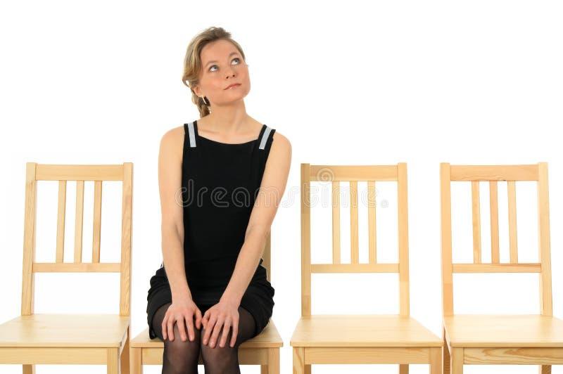 Jeune dame s'asseyant sur une présidence et une attente photo stock
