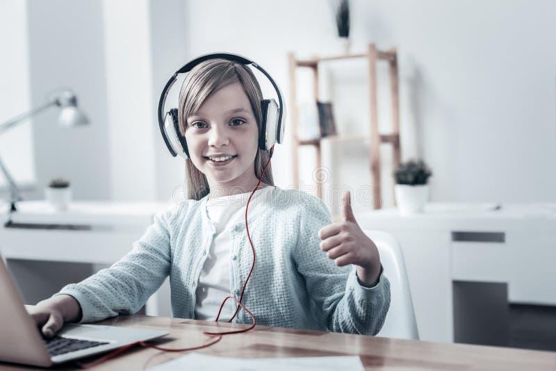 Jeune dame satisfaisante dans des écouteurs maniant maladroitement pour l'appareil-photo photographie stock libre de droits
