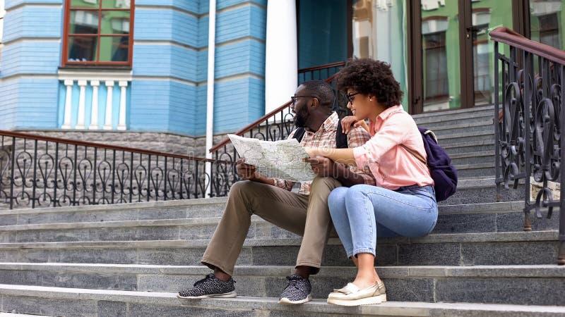 Jeune dame se dirigeant à la carte recherchant la direction avec l'ami, déplacement de couples photos stock