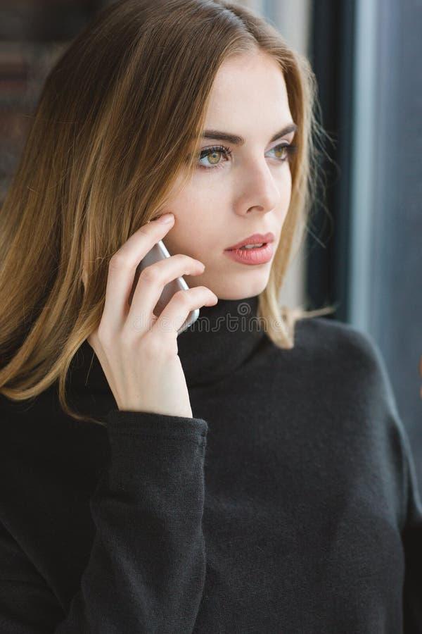 Jeune dame sereine attirante parlant au téléphone portable photo stock