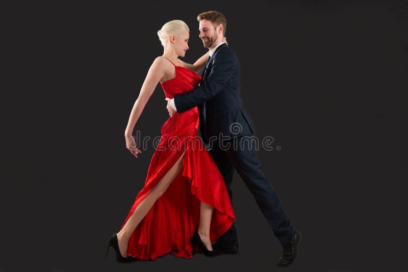 Jeune danse de couples sur le fond noir photos stock
