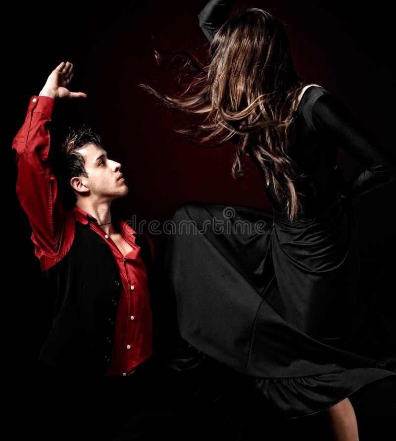 Jeune danse de flamenco de passion de couples sur le ligh rouge photos libres de droits