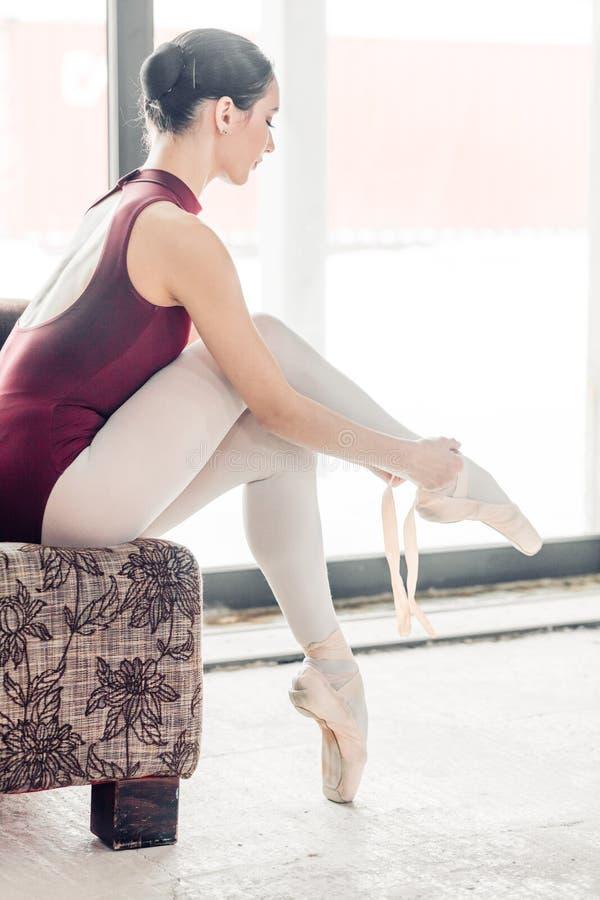 Jeune danseur mince mettant sur des chaussures de pointe tout en se reposant image libre de droits