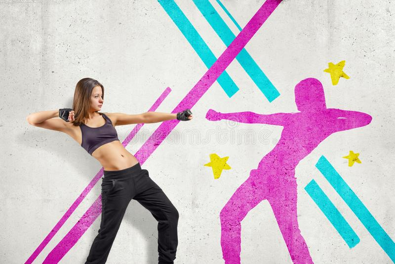 Jeune danseuse sportive de femme avec l'ombre pourpre sur les lignes colorées fond images libres de droits