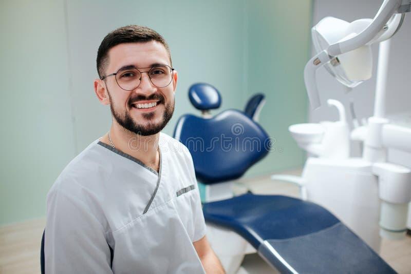 Jeune dentiste barbu positif se reposer dans la chambre et la pose d'art dentaire sur la caméra Il portent la robe longue et les  photographie stock