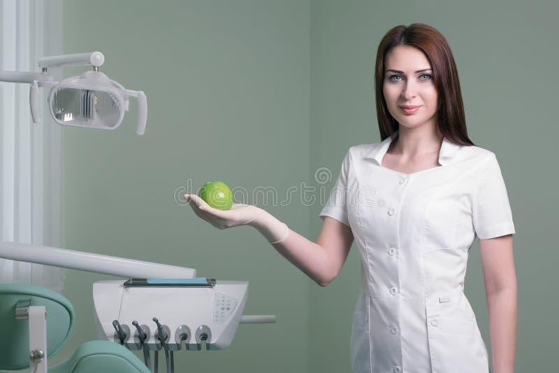 jeune dentiste féminin avec la pomme verte à disposition sur le fond du bureau médical photos libres de droits