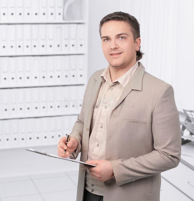 Jeune directeur avec des documents sur le fond du bureau photos libres de droits