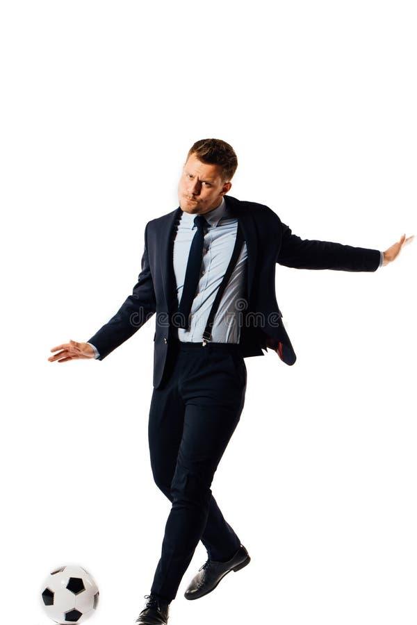 Jeune directeur beau d'homme d'affaires donnant un coup de pied un ballon de football sur le fond blanc d'isolement photographie stock libre de droits