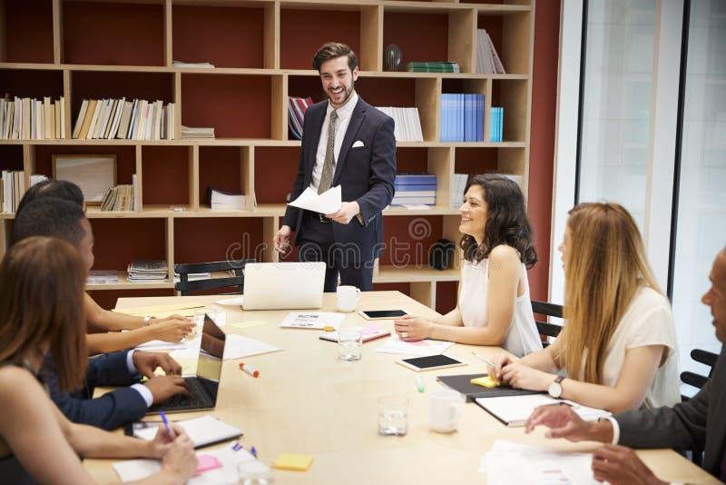 Jeune directeur masculin se tenant lors d'une réunion de salle de réunion d'affaires photo stock