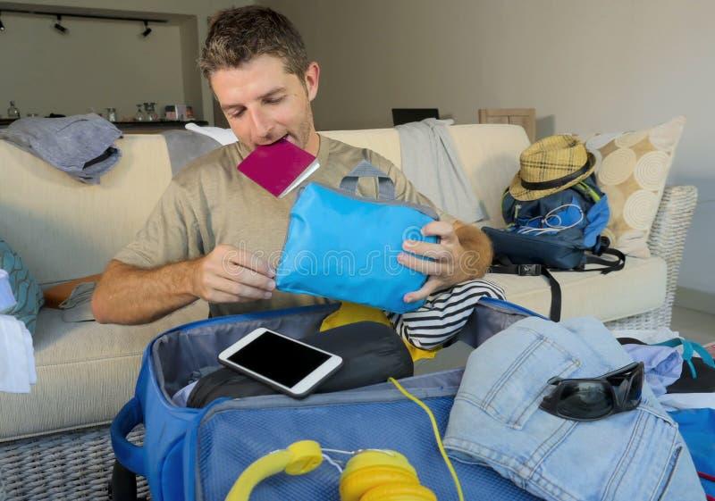 Jeune divan attrayant et heureux d'homme à la maison préparant le voyage de retour et emballant des vêtements se pliants de valis image libre de droits