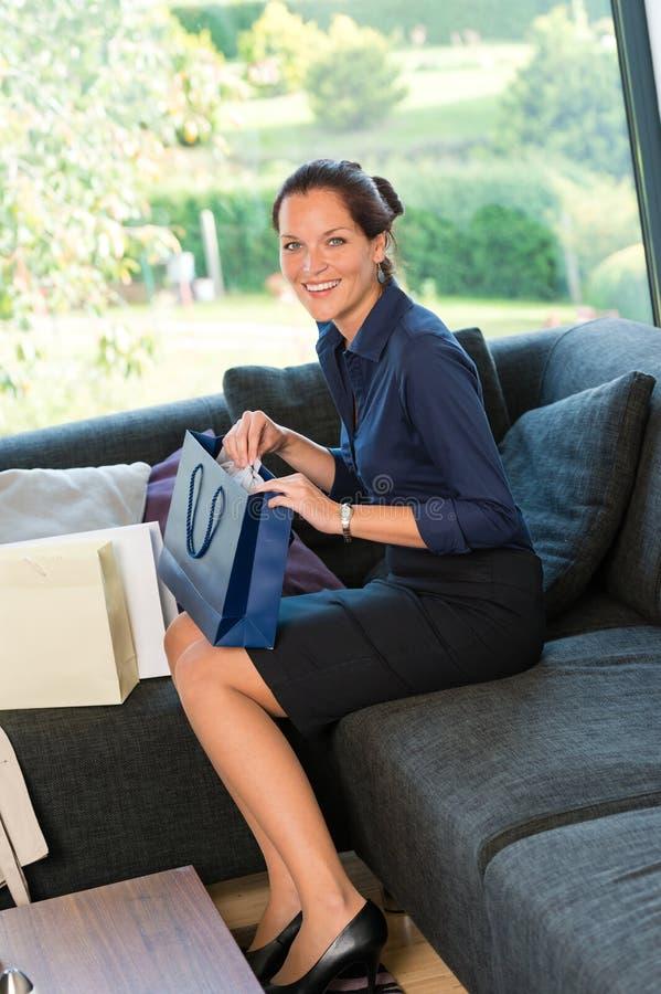 Jeune divan se reposant de sourire de sacs à provisions de femme photo stock