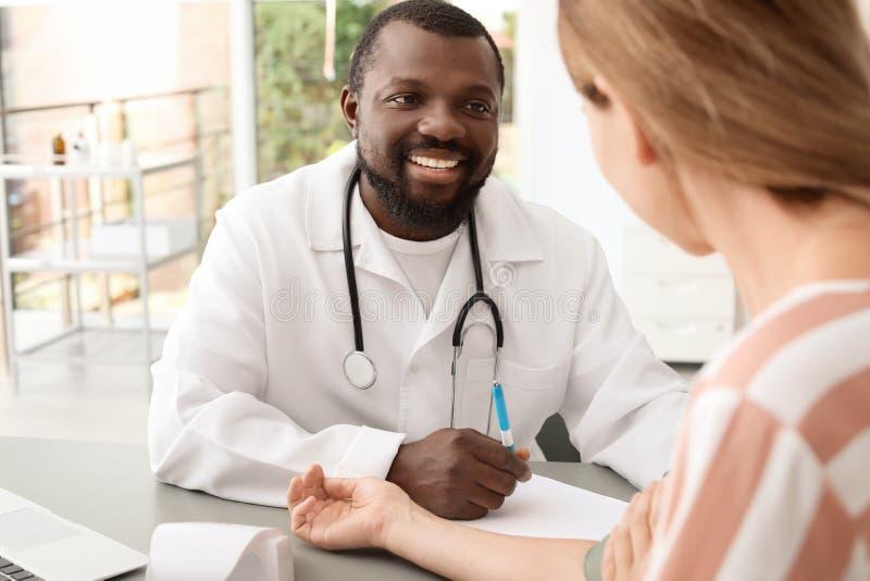 Jeune docteur afro-américain vérifiant le ` patient s image stock