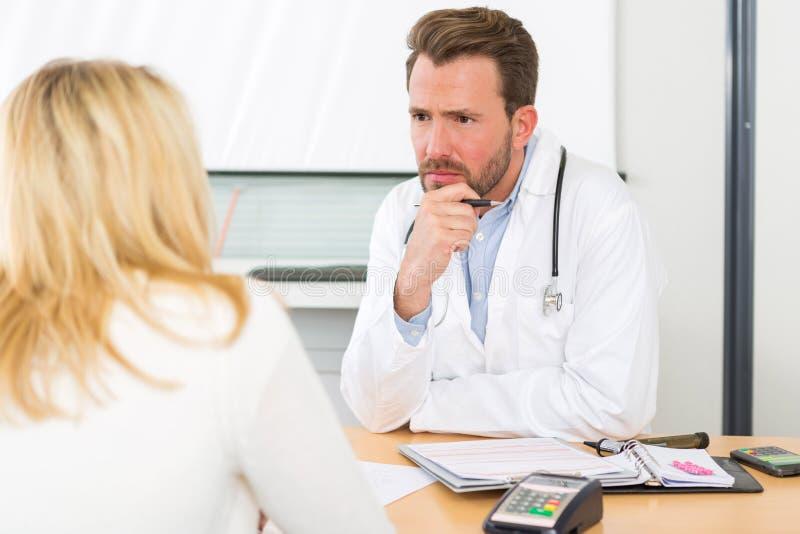 Jeune docteur attirant écoutant son patient photos stock