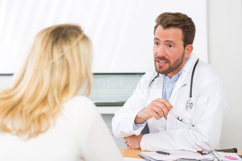 Jeune docteur attirant écoutant son patient photo stock