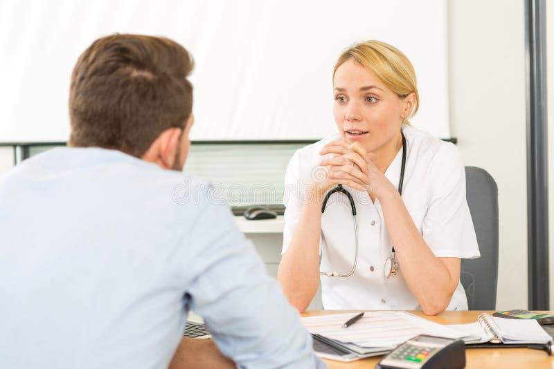 Jeune docteur attirant de femme écoutant son patient photographie stock