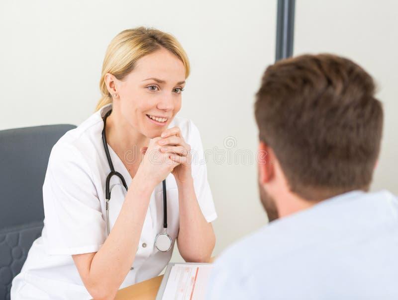 Jeune docteur attirant de femme écoutant son patient image stock