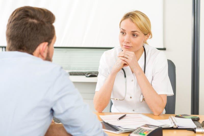 Jeune docteur attirant de femme écoutant son patient image libre de droits