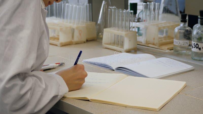 Jeune docteur de scientifique prenant des notes Le scientifique féminin prend des notes à l'arrière-plan sont les tubes photo stock