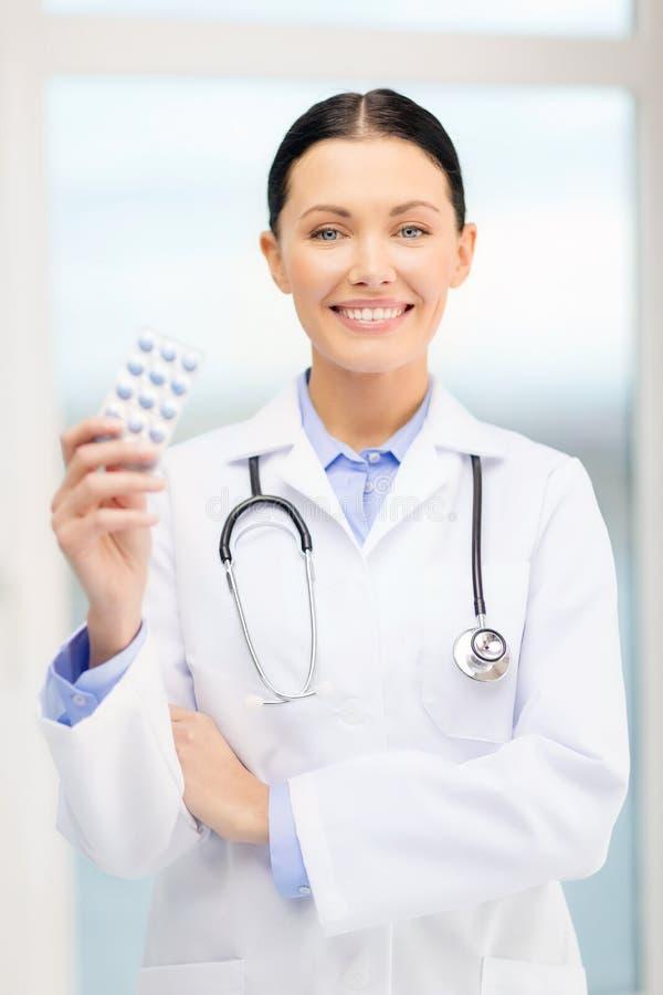 Jeune docteur de sourire avec les pilules et le sthethoscope images libres de droits