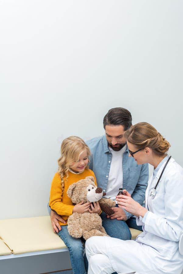 jeune docteur donnant le sirop à l'ours de nounours de photo stock